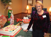 Beverly stands with her cake at her retirement party December 2013